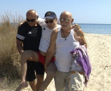 John's father and a friend from church help carry him after his baptism in the Aegean Sea. Members said they were delighted to have witnessed the ceremony. [Photo: Trans-European Division News]